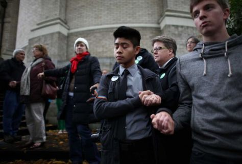 Robert Gavino, 19, prays with others as Catholics show support for marriage equality outside of Saint James Cathedral in Seattle.